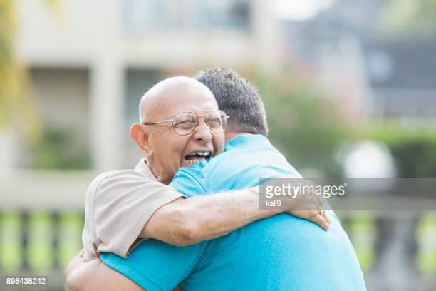 Hispanic man in his 90s, hugging adult grandson