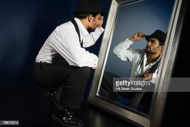 hispanic man in suit looking in mirror - vanity stock pictures, royalty-free photos & images