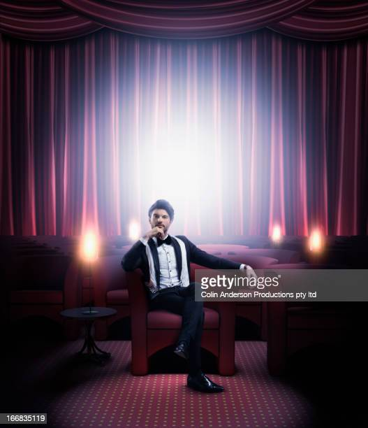 hispanic man in tuxedo sitting in empty lounge - actor stockfoto's en -beelden