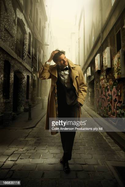 Hispanic man in tuxedo walking in city alleyway
