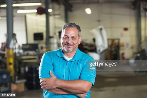 Hispanic man in vehicle repair shop
