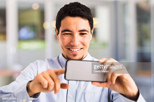 Hispanic man interacting with a mobile phone.