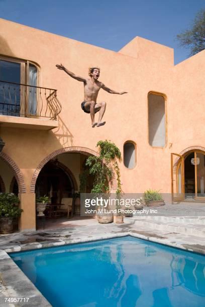 Hispanic man jumping into swimming pool