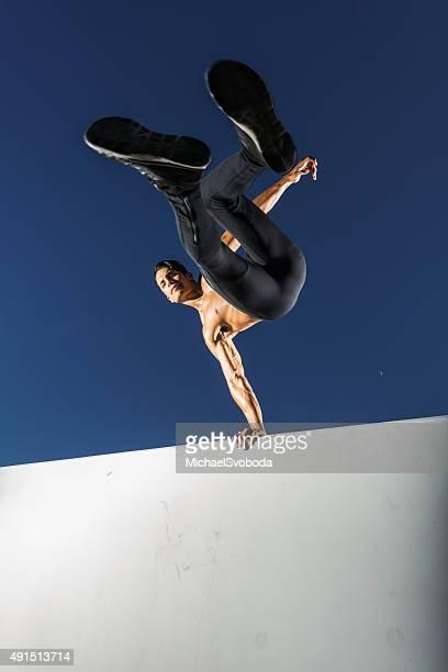 Hispanic Man Jumping Over A Wall
