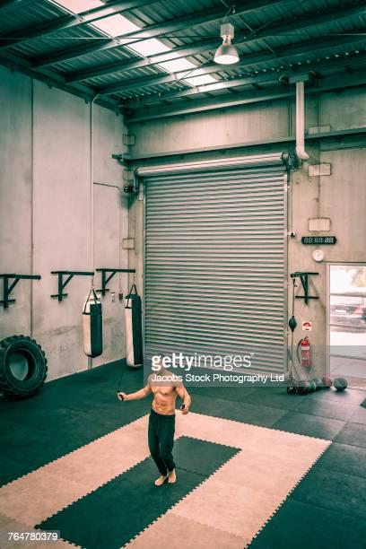 Hispanic man jumping rope in gymnasium