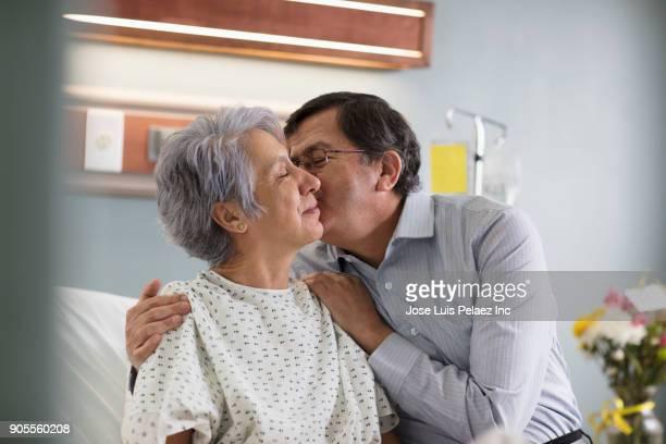 hispanic man kissing a woman on cheek in hospital bed - pareja abrazados cama fotografías e imágenes de stock