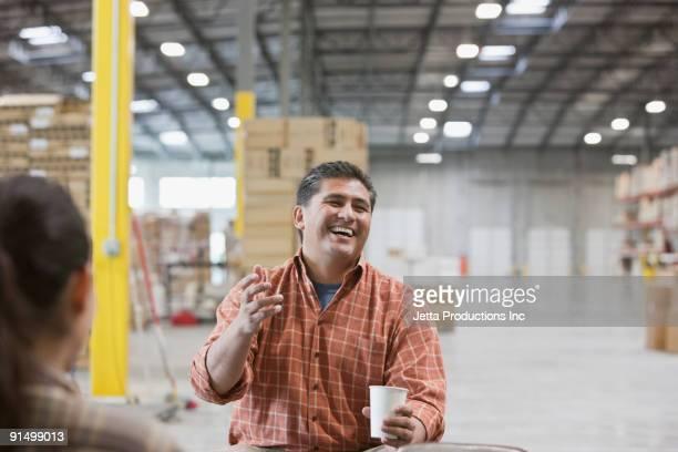 Hispanic man laughing and drinking coffee in warehouse