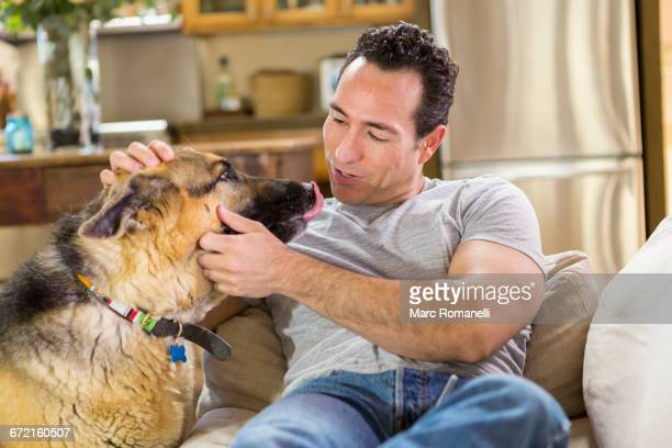 hispanic man laying on sofa petting dog - protruding stock pictures, royalty-free photos & images