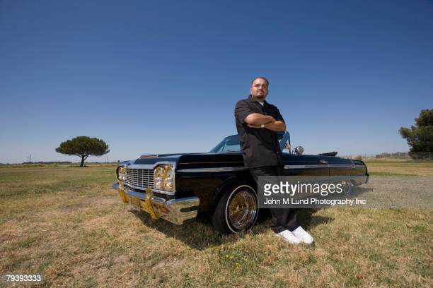 hispanic man leaning on low rider car - low rider stock pictures, royalty-free photos & images