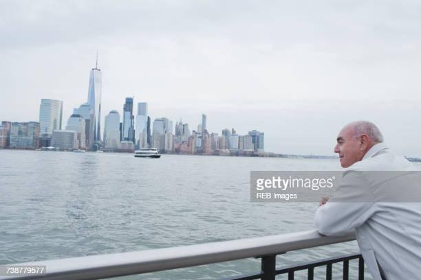 Hispanic man leaning on railing admiring scenic view of city
