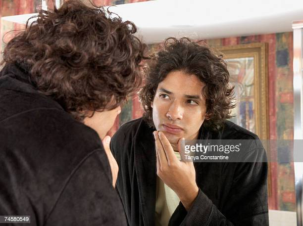 hispanic man looking in bathroom mirror - tanya constantine stock pictures, royalty-free photos & images