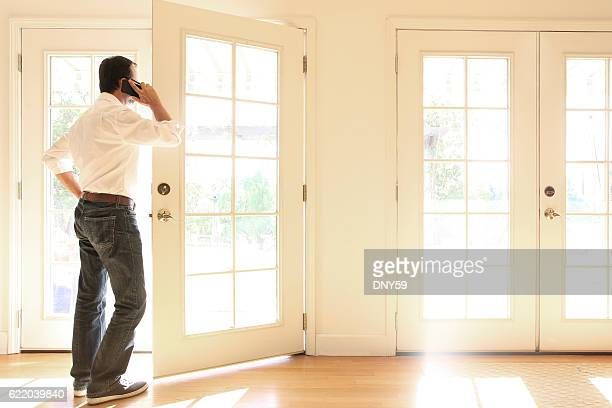 Hispanic Man Looking Out French Doors Talking On Cell Phone