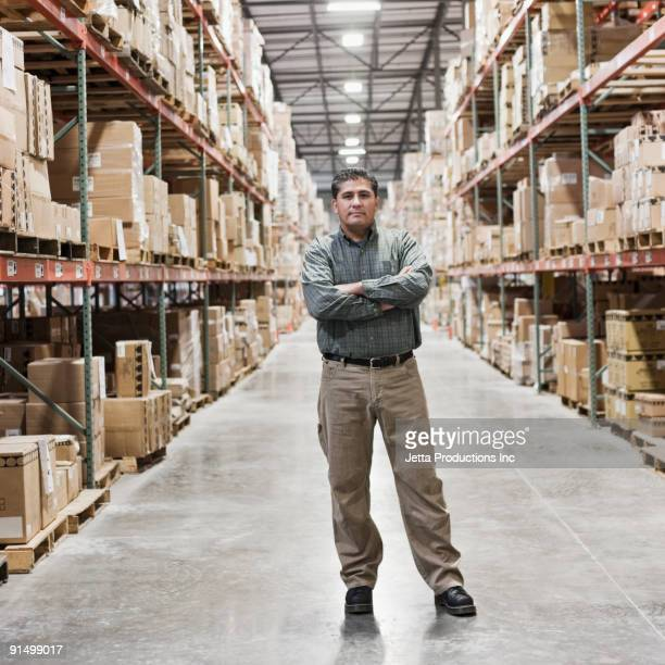 hispanic man looking serious in warehouse - one mature man only stock photos and pictures
