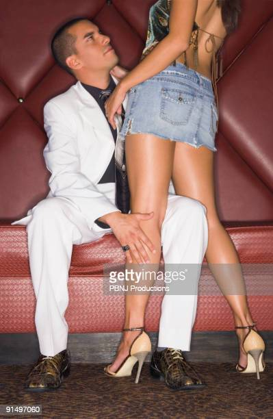 hispanic man looking up at girlfriend - man touching womans leg stock photos and pictures