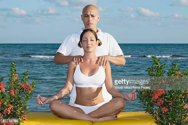 Hispanic man massaging meditating woman