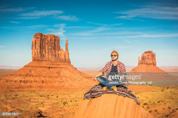Hispanic man meditating on hilltop in remote desert