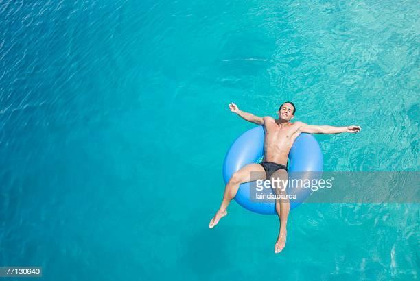 Hispanic man on float in water