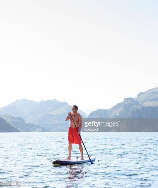 Hispanic man on paddleboard in river