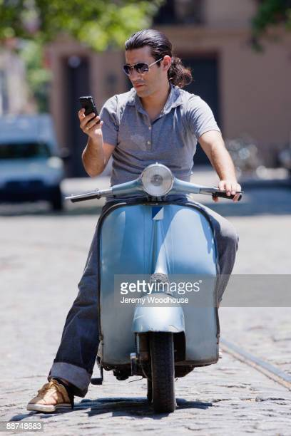 Hispanic man on scooter looking at cell phone
