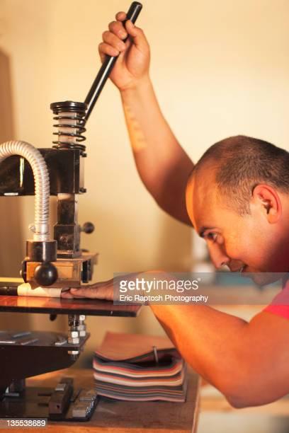 Hispanic man operating book-binding machine