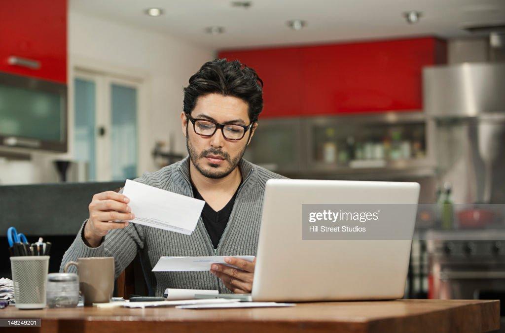Hispânico homem pagar contas no computador : Foto de stock