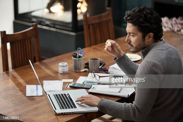 hispanic man paying bills on computer - one mid adult man only stock pictures, royalty-free photos & images