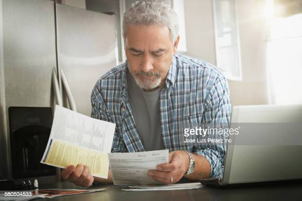 hispanic man paying bills on laptop in kitchen - financial bill stock pictures, royalty-free photos & images