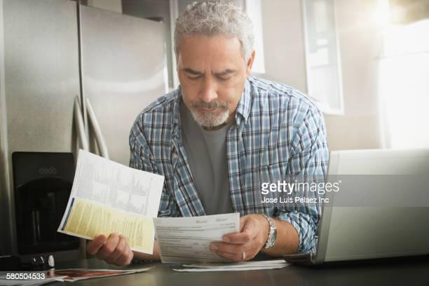 Hispanic man paying bills on laptop in kitchen