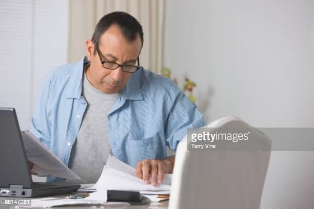 hispanic man paying bills - pilha arranjo - fotografias e filmes do acervo