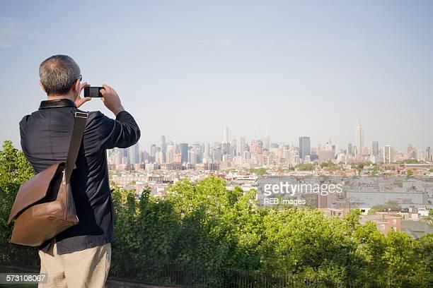 Hispanic man photographing New York cityscape, New York, United States