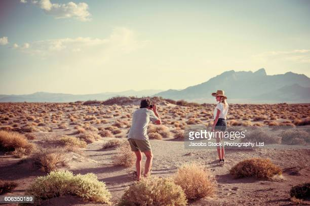 Hispanic man photographing wife in desert