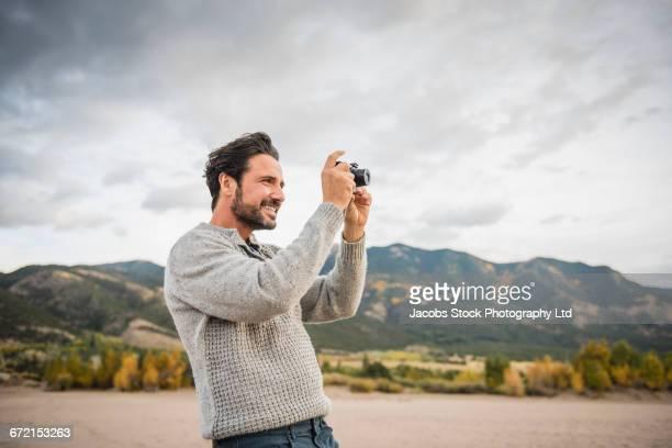 Hispanic man photographing with digital camera at mountains