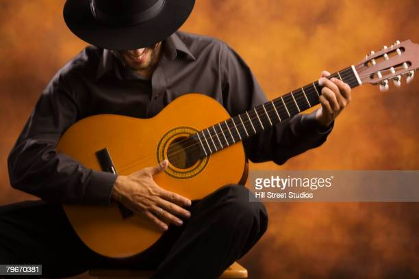 hispanic man playing acoustic guitar - flamenco stock photos and pictures