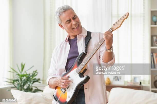 Hispanic man playing electric guitar in living room