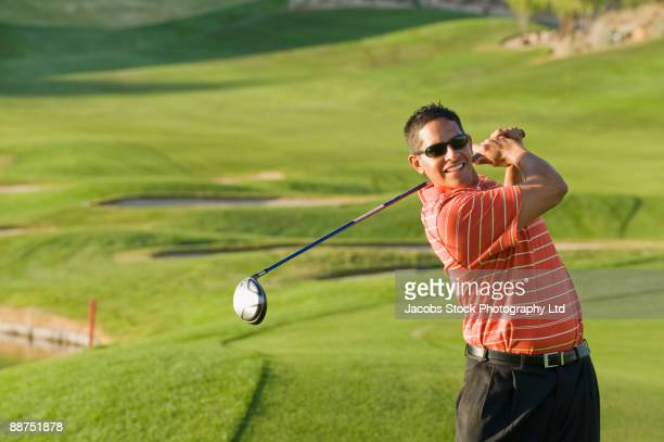 hispanic man playing golf - golf swing stock pictures, royalty-free photos & images