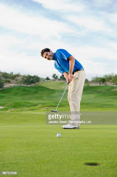 hispanic man playing golf - putting stock pictures, royalty-free photos & images