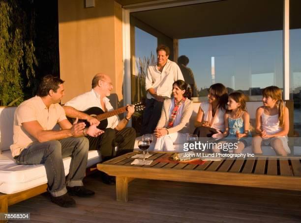 Hispanic man playing guitar for family