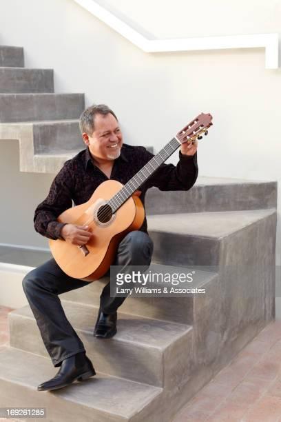 Hispanic man playing guitar on steps