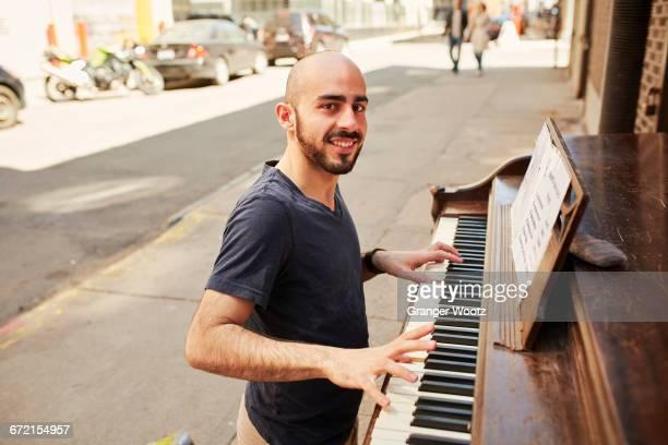 Hispanic man playing piano on city sidewalk