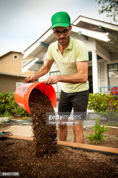 Hispanic man pouring bucket of dirt in raised garden