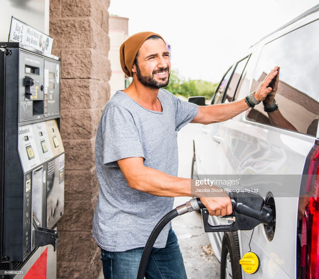 Hispanic man pumping gas : Stock Photo