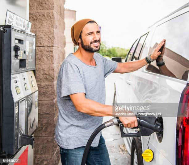 Hispanic man pumping gas