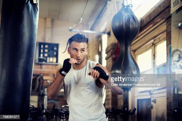 Hispanic man punching speed bag in gymnasium