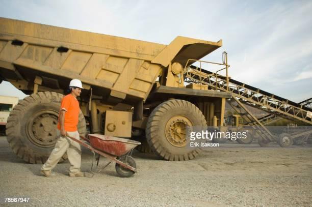 Hispanic man pushing wheelbarrow at gravel plant