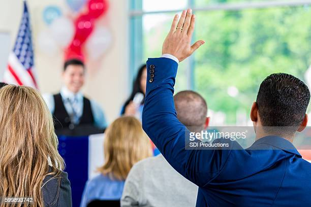 hispanic man raising hand during political town hall meeting - rathaus stock-fotos und bilder
