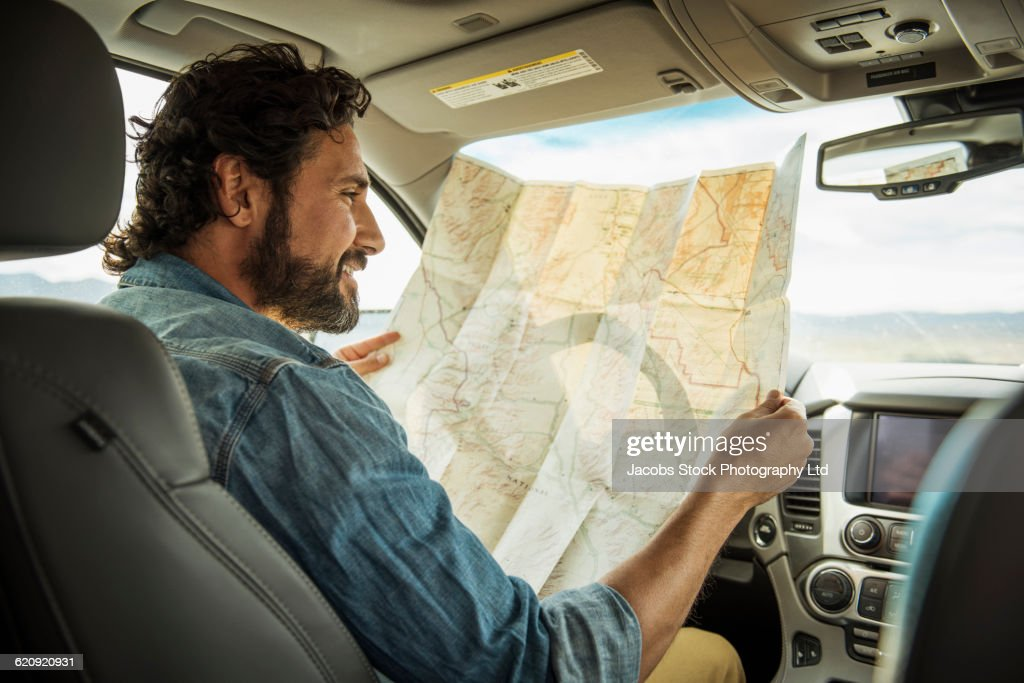 Hispanic Man Reading Map In Car High-Res Stock Photo - Getty ... on navigation in car, water in car, time in car, entertainment in car,