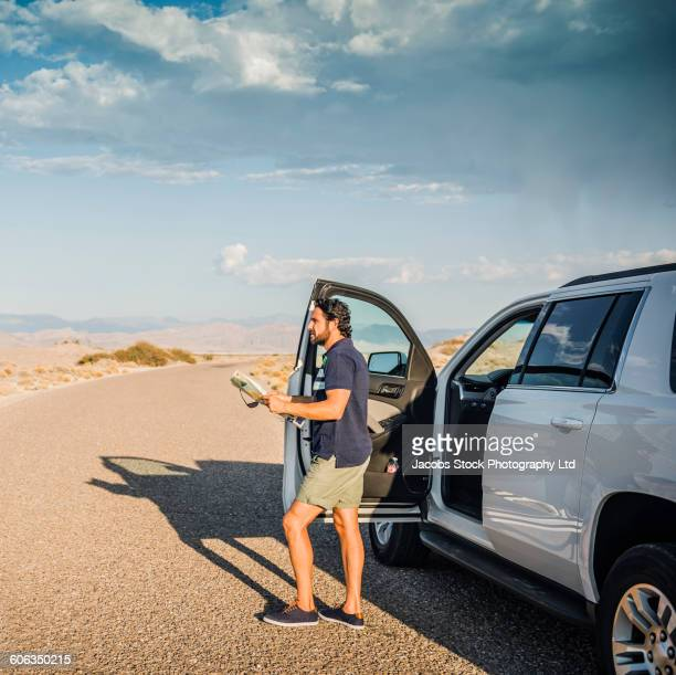 Hispanic man reading map on remote road