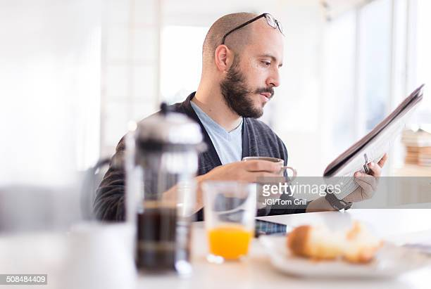 Hispanic man reading newspaper at breakfast
