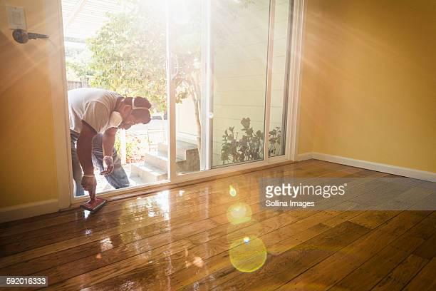 Hispanic man refinishing floors in new house