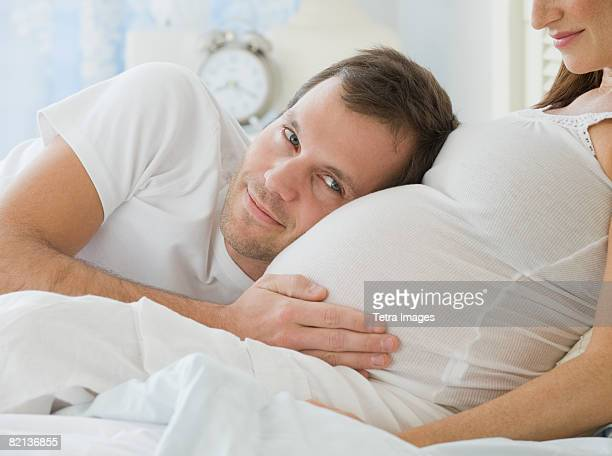 Hispanic man resting head on pregnant wife
